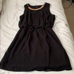 Short black chiffon dress with gold bar necklace